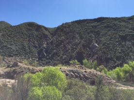 The remains of the Tombstone lie at the foot of the east abutment. Although vegetation has covered these hills in the years since the collapse, the ridge where the hillside gave way is still visible.